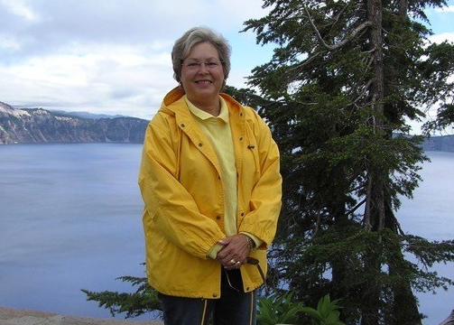 A smiling woman stands in a scenic location wearing a yellow coat